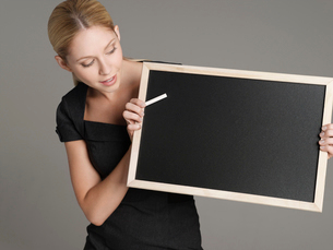 Portrait of young female teacher holding blackboardの写真素材 [FYI03631341]