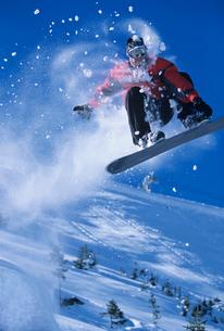 Snowboarder mid-air above ski Slope  snow powder trailingの写真素材 [FYI03631346]