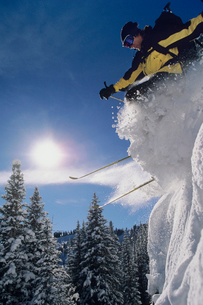 Skier skiing through snow  jumping from snow bankの写真素材 [FYI03631355]