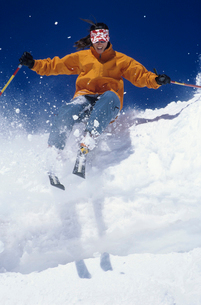Skier skiing through snow  jumping from snow bankの写真素材 [FYI03631361]