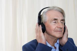 Senior man wearing headphones  head and shoulders  in studの写真素材 [FYI03631445]