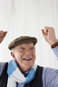 Senior man in football scarf  celebrating in studio  headの写真素材 [FYI03631452]