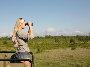 Young woman on safari  standing in jeep  looking through bの写真素材 [FYI03631485]