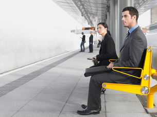 Businesspeople sitting on benches  Waiting at Train Statioの写真素材 [FYI03631521]