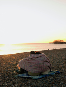 Couple wrapped in blanket sitting on beach  watching sunseの写真素材 [FYI03631528]