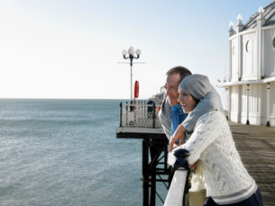 Couple standing on pier looking out at seaの写真素材 [FYI03631530]