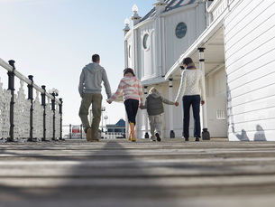 Family holding hands  walking along pier  back view  low aの写真素材 [FYI03631541]