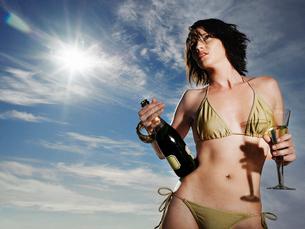 Woman in bikini holding champagne outdoorsの写真素材 [FYI03631592]