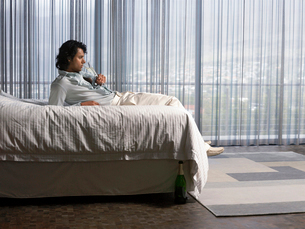 Man reclining on bed sipping champagne in bedroomの写真素材 [FYI03631604]