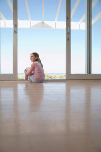 Girl sitting on floor in doorway  smilingの写真素材 [FYI03631619]