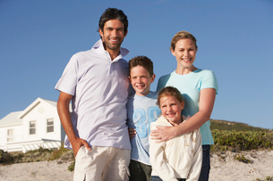 Family standing on beach smiling  beach house behindの写真素材 [FYI03631639]