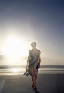 Woman walking on beach against sunsetの写真素材 [FYI03631674]
