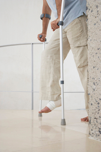 Injured man with wrapped ankle on crutches  low sectionの写真素材 [FYI03631678]