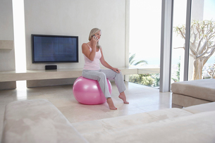 Mature woman sitting on exercise ball in living room  talkの写真素材 [FYI03631688]