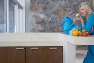 Mature woman leaning on countertop  eating apple  side vieの写真素材 [FYI03631693]