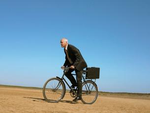 Businessman riding bicycle in desertの写真素材 [FYI03631740]
