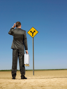 Businessman looking at road sign in desert  back viewの写真素材 [FYI03631744]