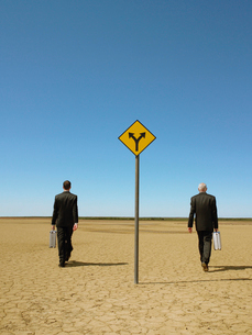 Two businessmen with briefcases walking past road sign inの写真素材 [FYI03631754]