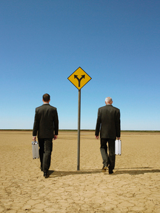 Two businessmen with briefcases walking past road sign inの写真素材 [FYI03631755]