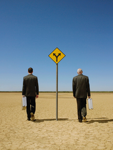 Two businessmen with briefcases walking past road sign inの写真素材 [FYI03631756]