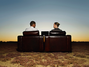 Two business people in armchairs in open plain at sunsetの写真素材 [FYI03631766]