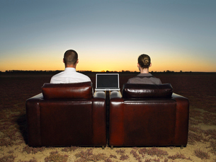 Two business people sitting in armchairs in open plain atの写真素材 [FYI03631767]