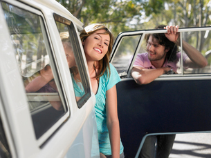 Couple leaning out of van parked by side of roadの写真素材 [FYI03631795]