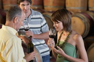 Three people wine-tasting beside wine casksの写真素材 [FYI03631817]