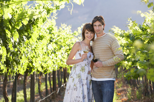 Young couple with wine glasses in vineyardの写真素材 [FYI03631835]