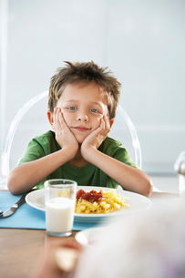 Young boy with head in hands at dinner tableの写真素材 [FYI03631848]