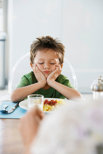 Young boy with head in hands at dinner tableの写真素材 [FYI03631849]