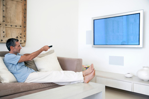 Man using remote control  reclining on couch in living rooの写真素材 [FYI03631876]