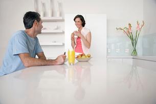 Couple having breakfast at kitchen benchの写真素材 [FYI03631877]
