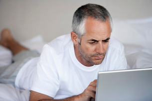 Man using laptop  lying on stomach on bedの写真素材 [FYI03631892]