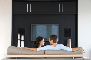 Couple sitting in front of flat screen television in livinの写真素材 [FYI03631904]