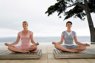 Two women sitting in yoga positions on terraceの写真素材 [FYI03631907]