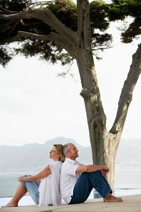 Couple sitting back to back on edge of infinity pool  sideの写真素材 [FYI03631912]