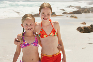 Two girls (7-9  10-12) posing on beach  portraitの写真素材 [FYI03631955]