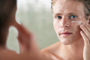 Man applying facial cream in front of mirrorの写真素材 [FYI03632046]