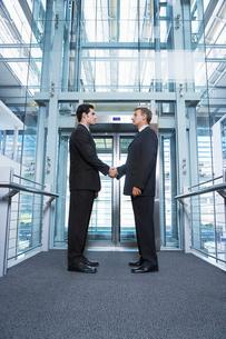 Businessmen shaking hands in office buildingの写真素材 [FYI03632075]