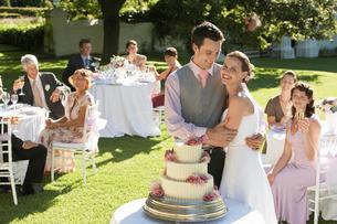 Mid adult bride and groom in garden among wedding guestsの写真素材 [FYI03632103]