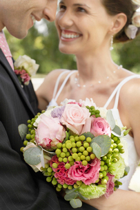 Mid adult bride and groom in garden  smiling  close-upの写真素材 [FYI03632118]