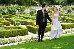 Bride and groom walking hand in hand in gardenの写真素材 [FYI03632119]