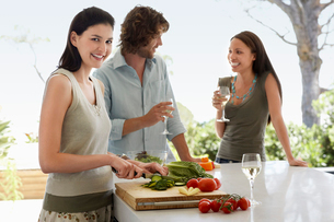 Friends talking   drinking wine  preparing food at a dinneの写真素材 [FYI03632126]