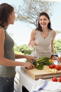 Friends talking   drinking wine  preparing food at a dinneの写真素材 [FYI03632127]