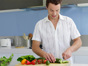 Young man cutting vegetables on cutting board in kitchenの写真素材 [FYI03632138]