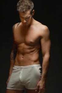 man wearing underwear  on black background  portraitの写真素材 [FYI03632163]