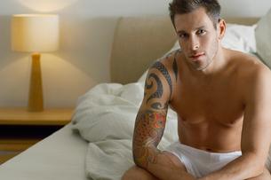 Semi naked man sitting on bed  portraitの写真素材 [FYI03632168]