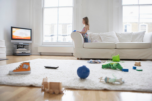 Girl (5-6) watching television  toys on floor in foregrounの写真素材 [FYI03632298]