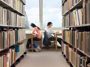 Teenagers doing homework in libraryの写真素材 [FYI03632364]